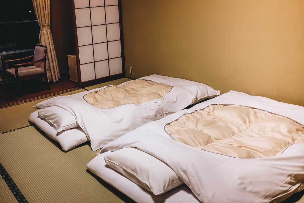 Interior of a Japanese bedroom with futons and tatami on the floor.