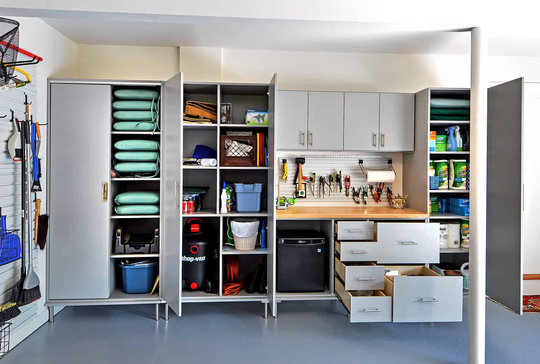 Garage store system with cabinet doors and drawers opened to reveal just how spacious the storage spaces are.