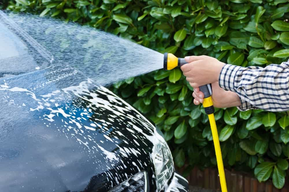 Hands holding a garden hose to wash the car.