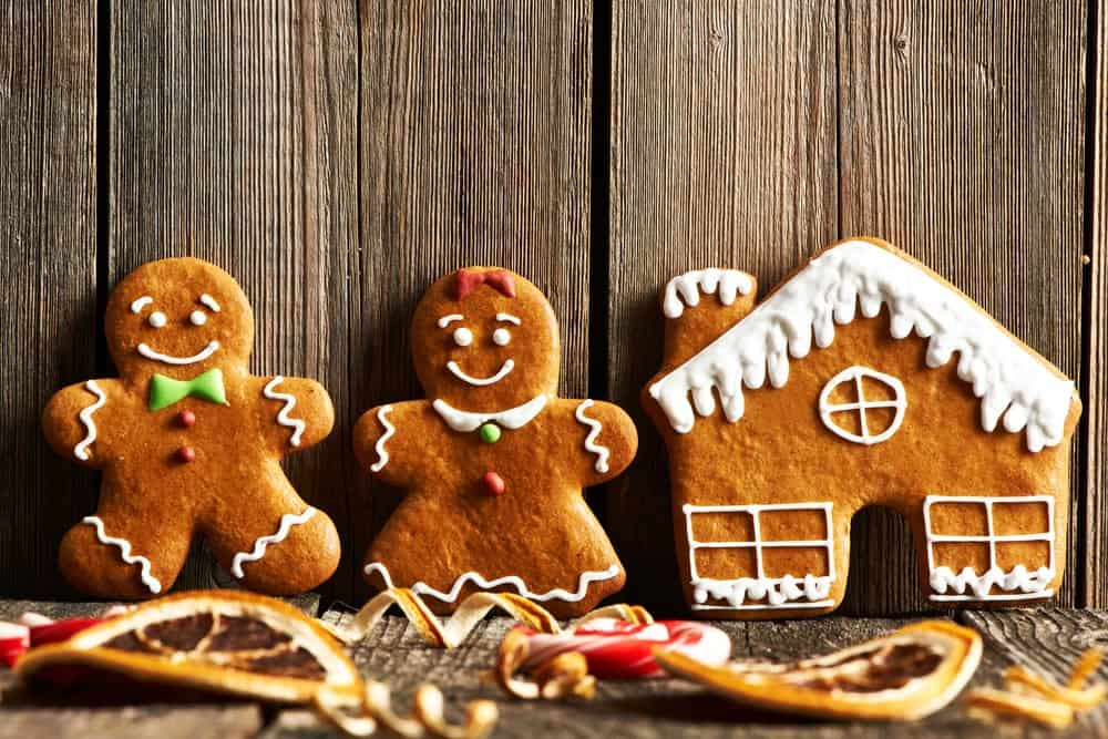Gingerbread man, woman, and house cookies on wooden background.