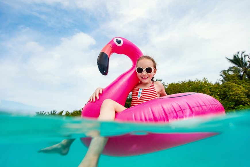 A girl is on her pink inflatable swan as she prepares to swim into the sea.