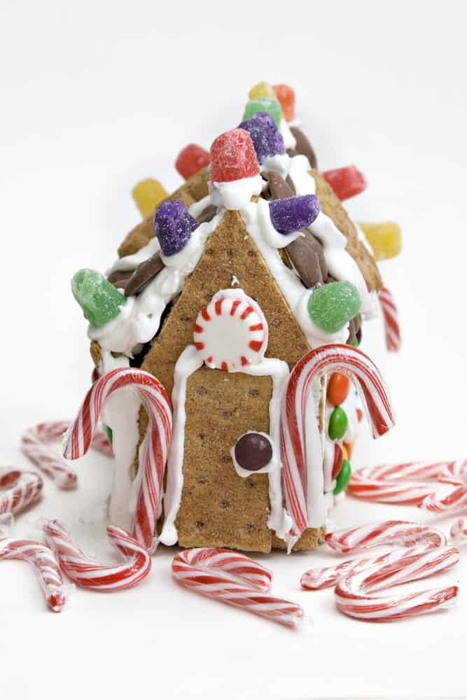 Gingerbread house made of Graham crakers decorated with candy canes and colorful candies.