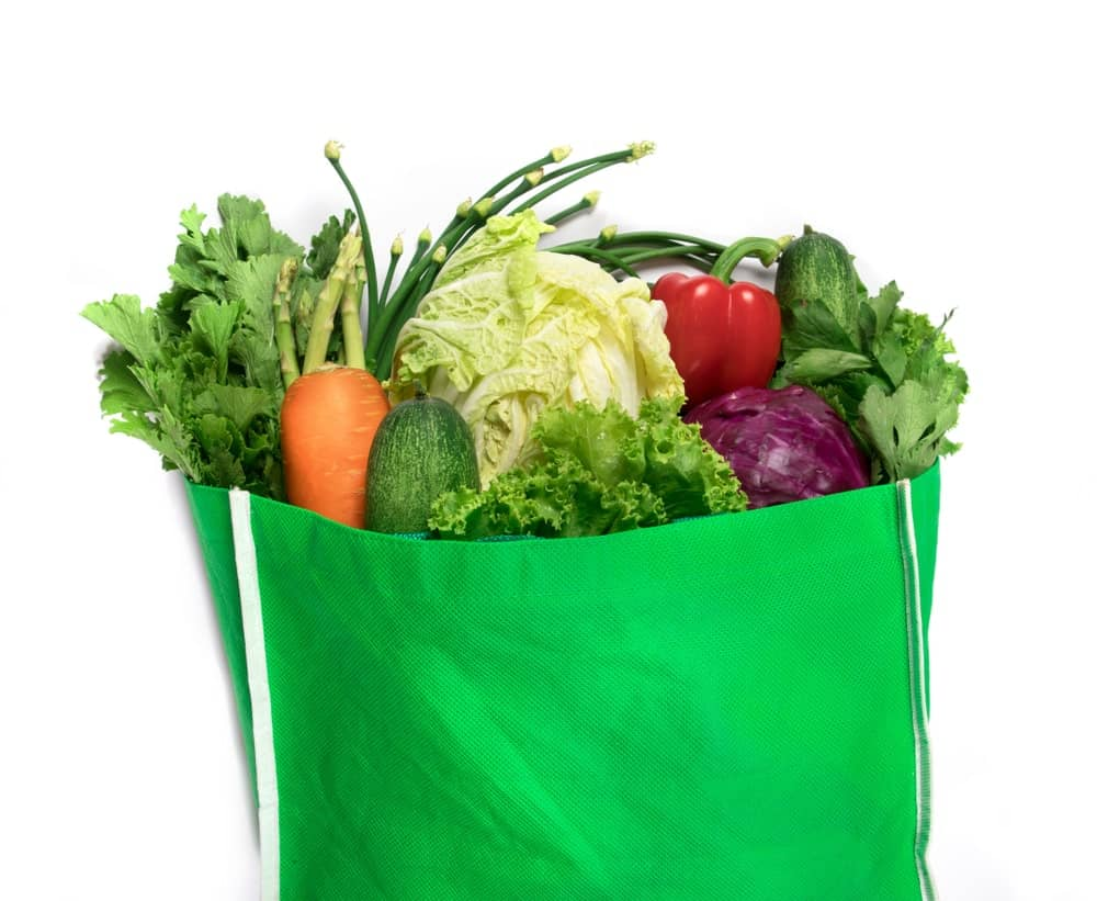 Green bag filled with a variety of vegetables