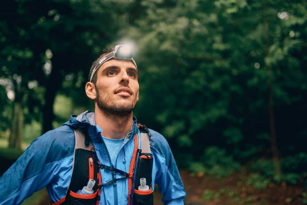 Man wearing headlamp flashlight in the woods.