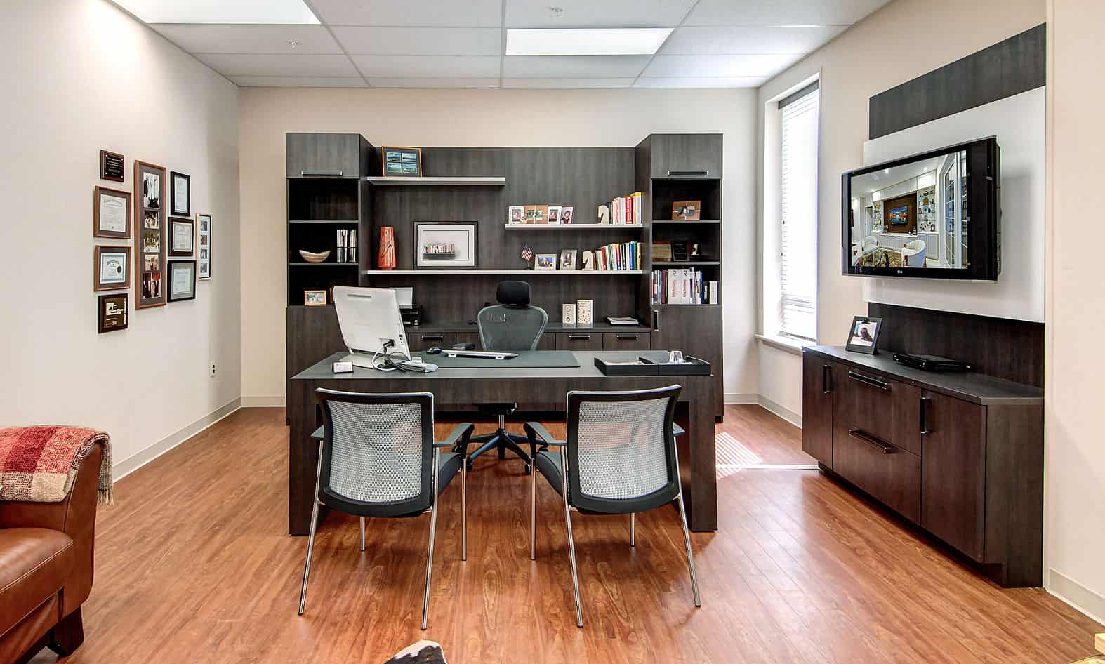 Large home office with custom cabinetry, open shelving, built-in desk, and a table with chairs.