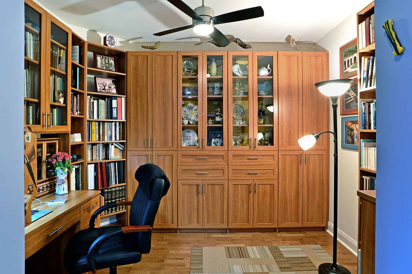 A classy home office with a built-in desk with the same finish as the cabinetry and bookshelves. The hardwood flooring fits well with the room instead.