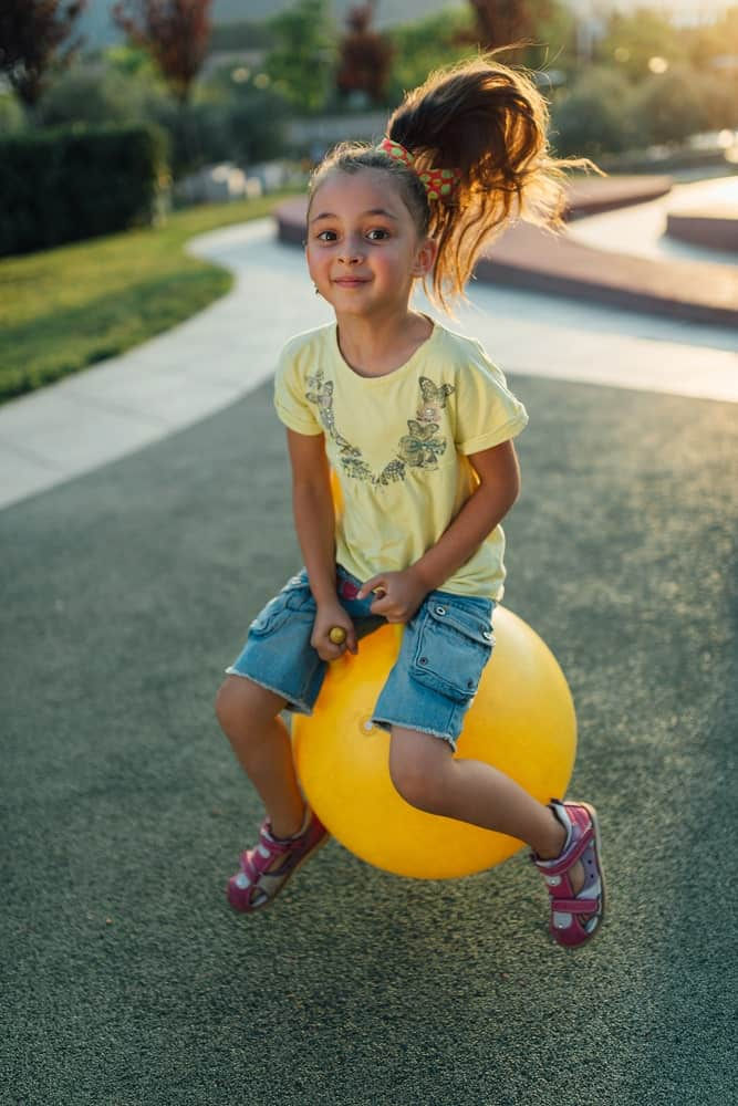A girl is bouncing outside of her house using her hopper ball.