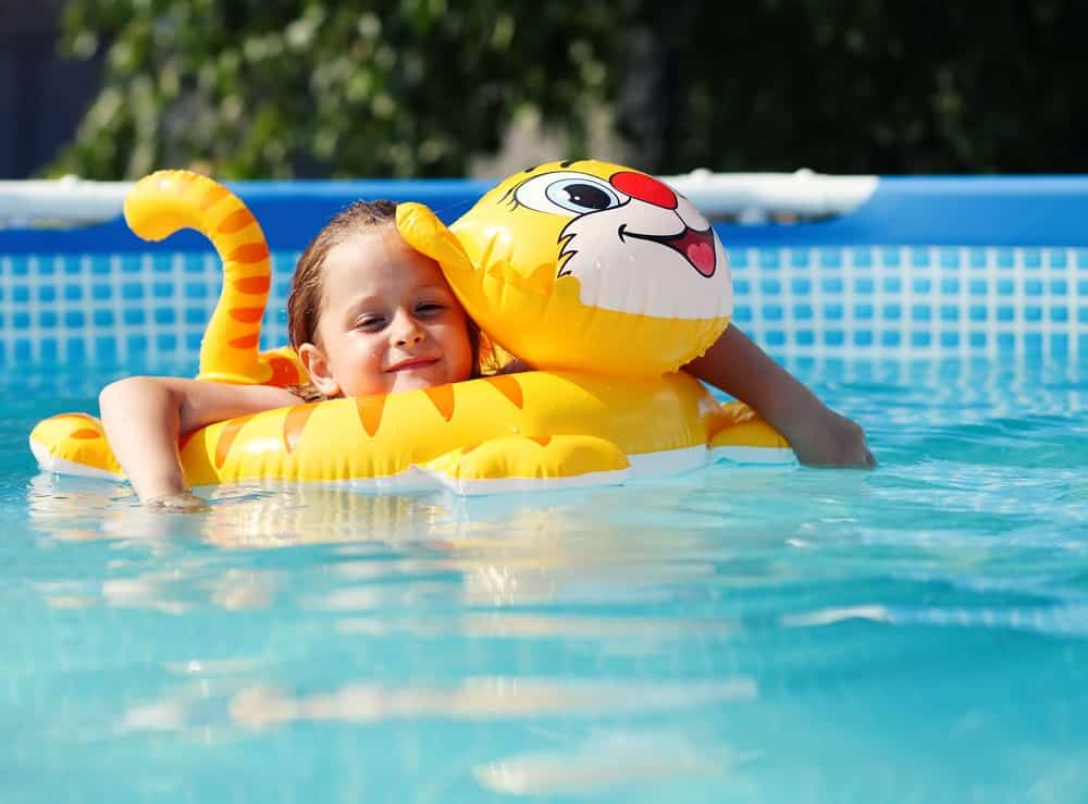 A girl is swimming with her inflatable toy.
