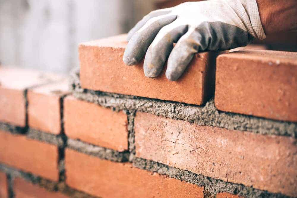 A gloved hand lays a brick on the brick structure being built up.