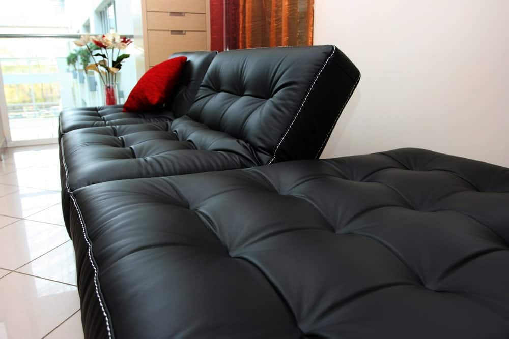 Leather tufted sofa bed with red throw pillow.
