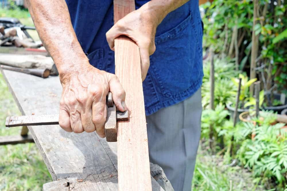 Marking gauge used with a piece of wood.