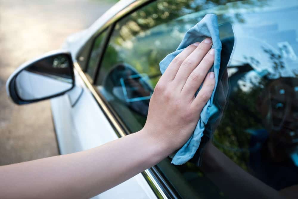 Hand holding a microfiber glass towel to wipe the car door window.