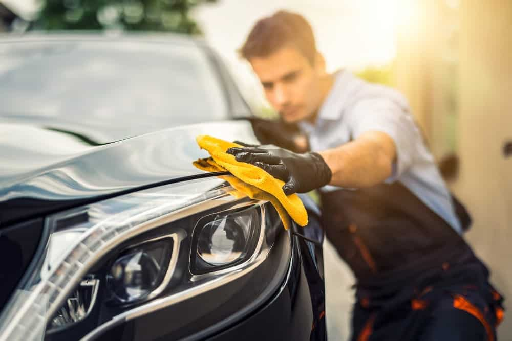 Man wiping a car with a microfiber towel.