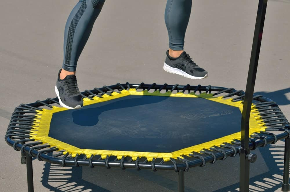 A lady is doing her workout routine using a mini trampoline.