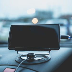Mobile phone charging plugged on car console.