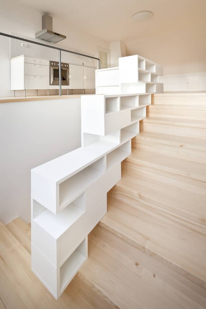 modern basement stairs with shelving balustrade.