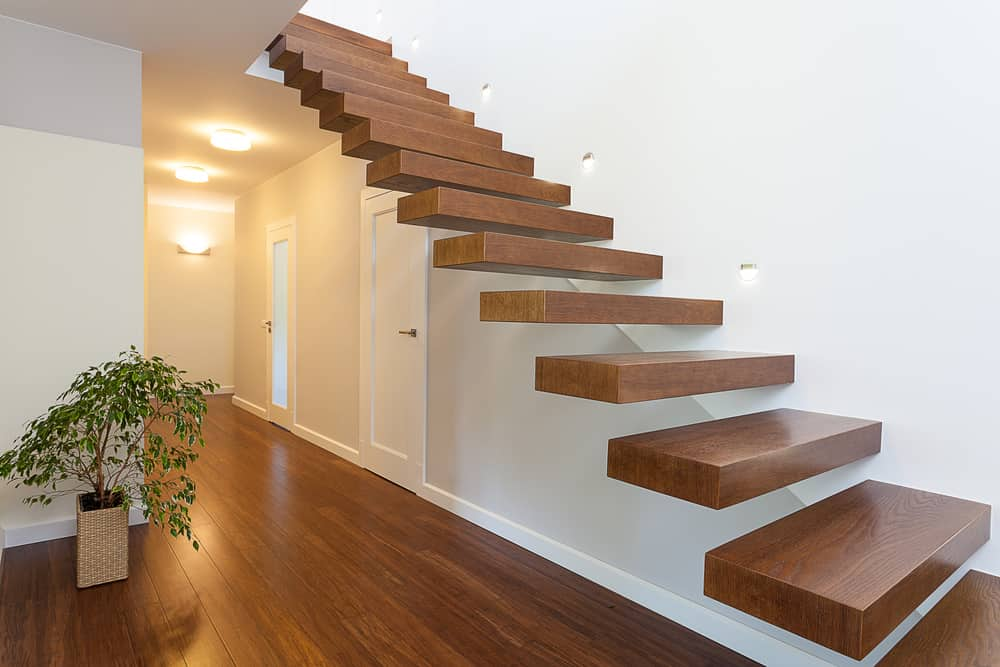 Modern illuminted wood stairs against a white wall and no balustrade.