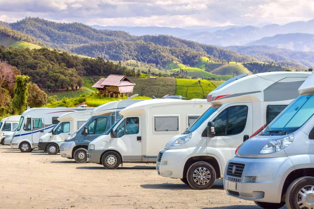 A row of different types of motorhomes with mountains at a distance.
