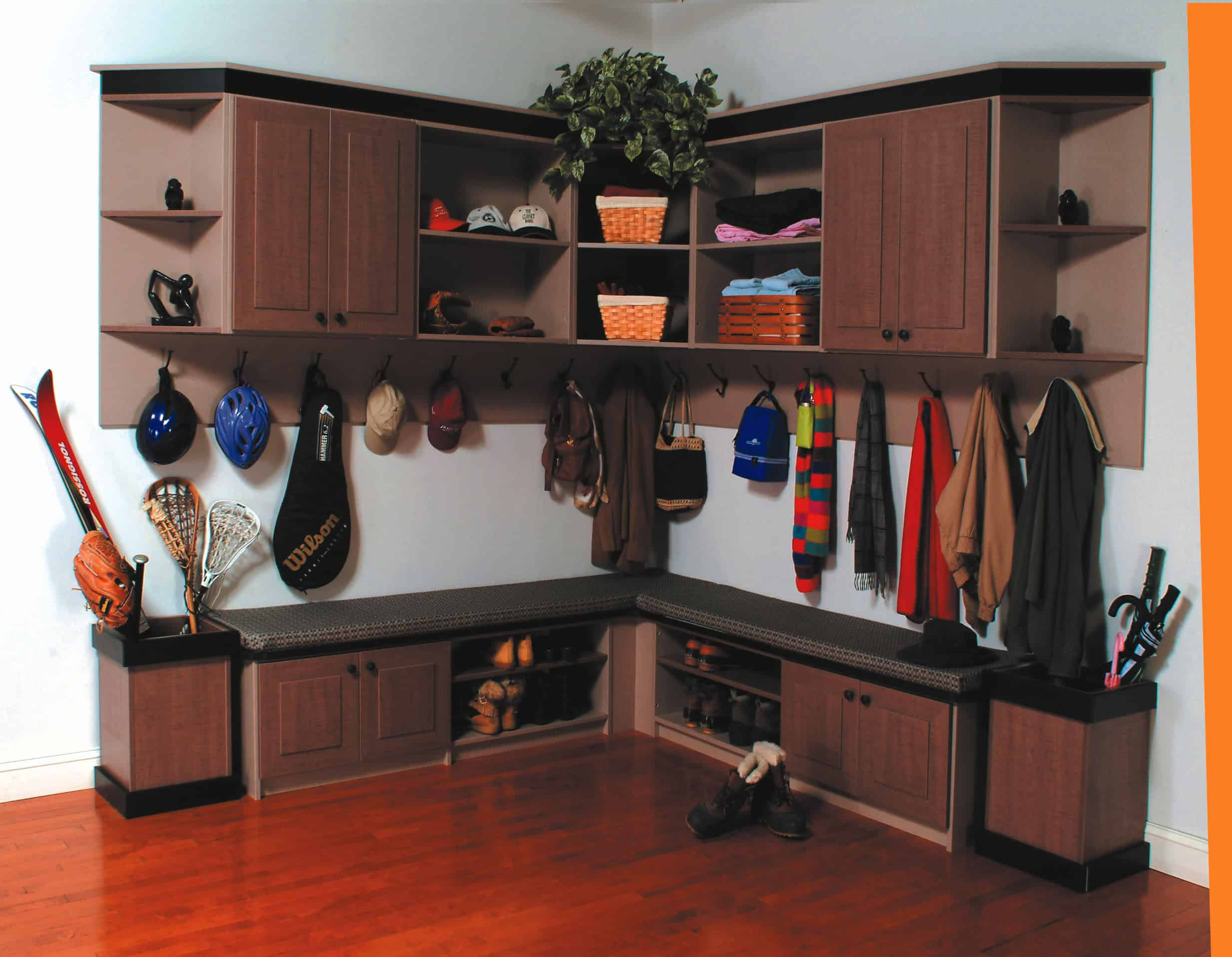Small mudroom with built-in seating, upper and lower cabinets, open shelving, wall hooks, and storage boxes for umbrellas and other items.