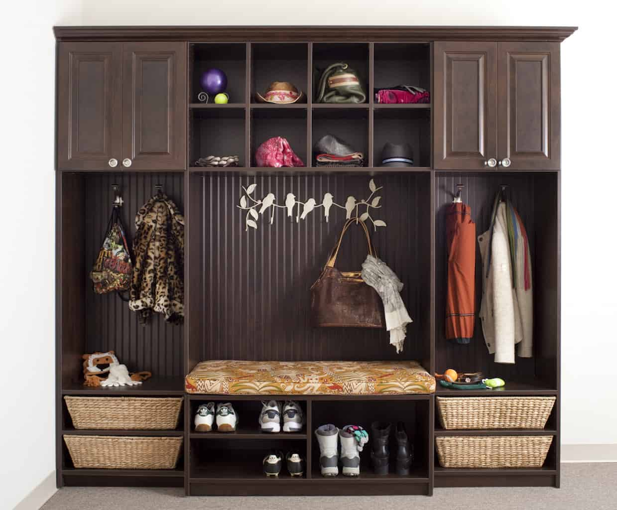 Custom-built mudroom with a small seating, shoe storage, wall hooks, open shelving, and upper cabinets.