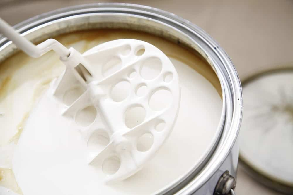 Mixing the oil-based warm white paint using a stirrer.