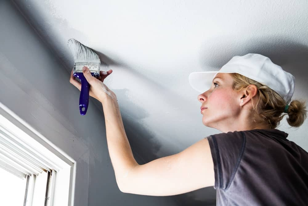 A lady is painting the edges of a ceiling using a paint brush.