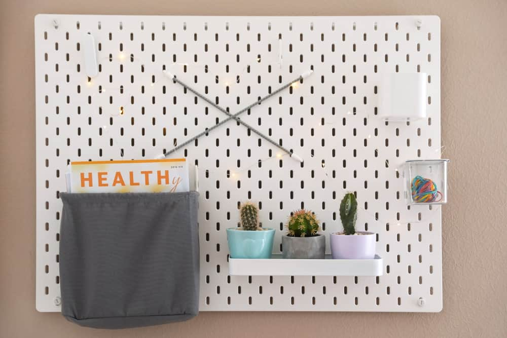 Pegboard used as storage and organization corner for shelf, containers, and drawstring bag.