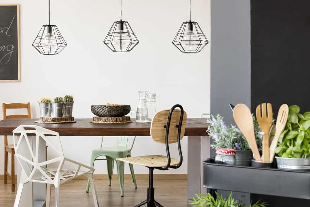 A trio of pendant lights hang above a dining table.