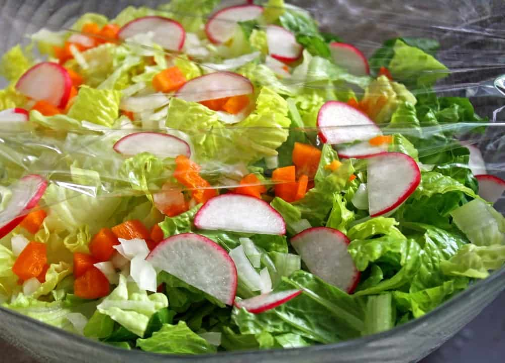 A plastic wrap is used to maintain the freshness of the salad.