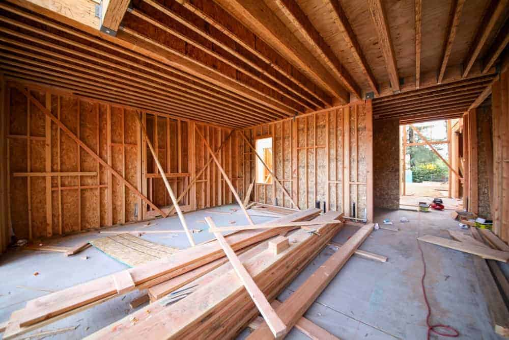 This is a wood framing interior work in progress with wood walls and ceiling and plywood sheathing on a new construction building.