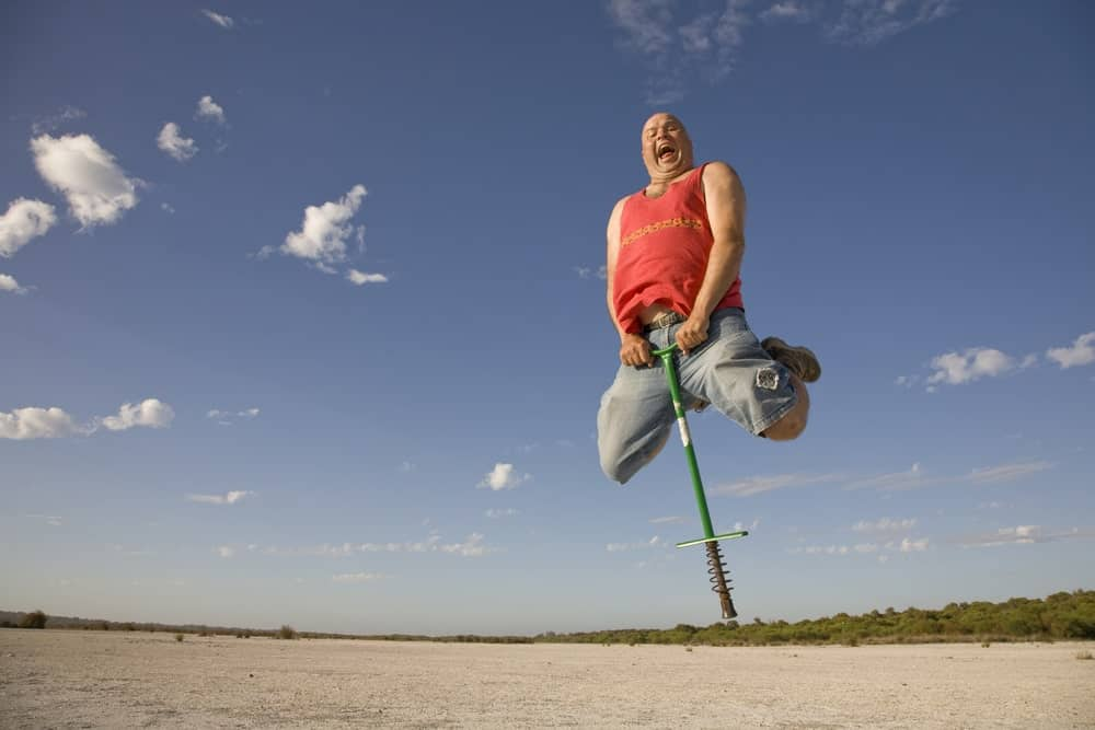 A man is having a thrilling experience while bouncing using a pogo stick.