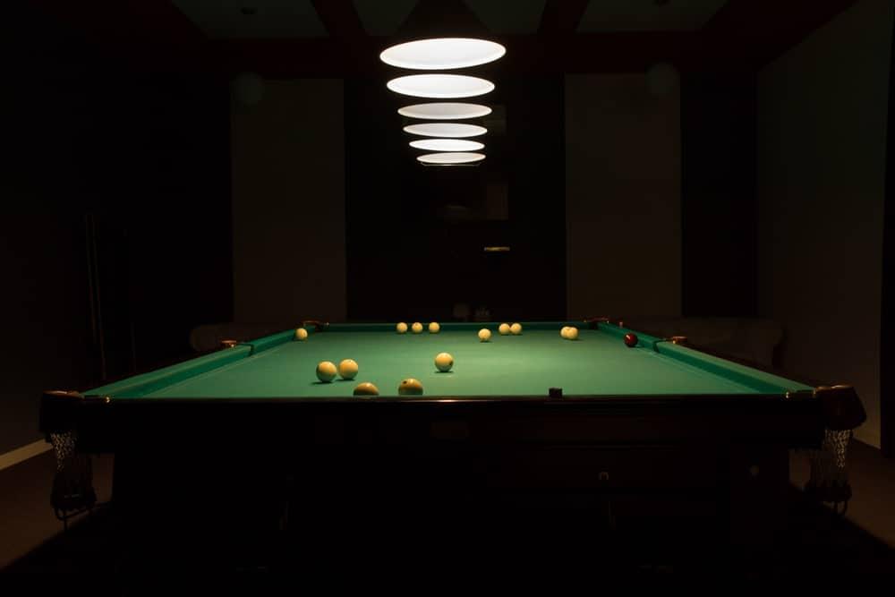 Pendant lights shine on the pool table.