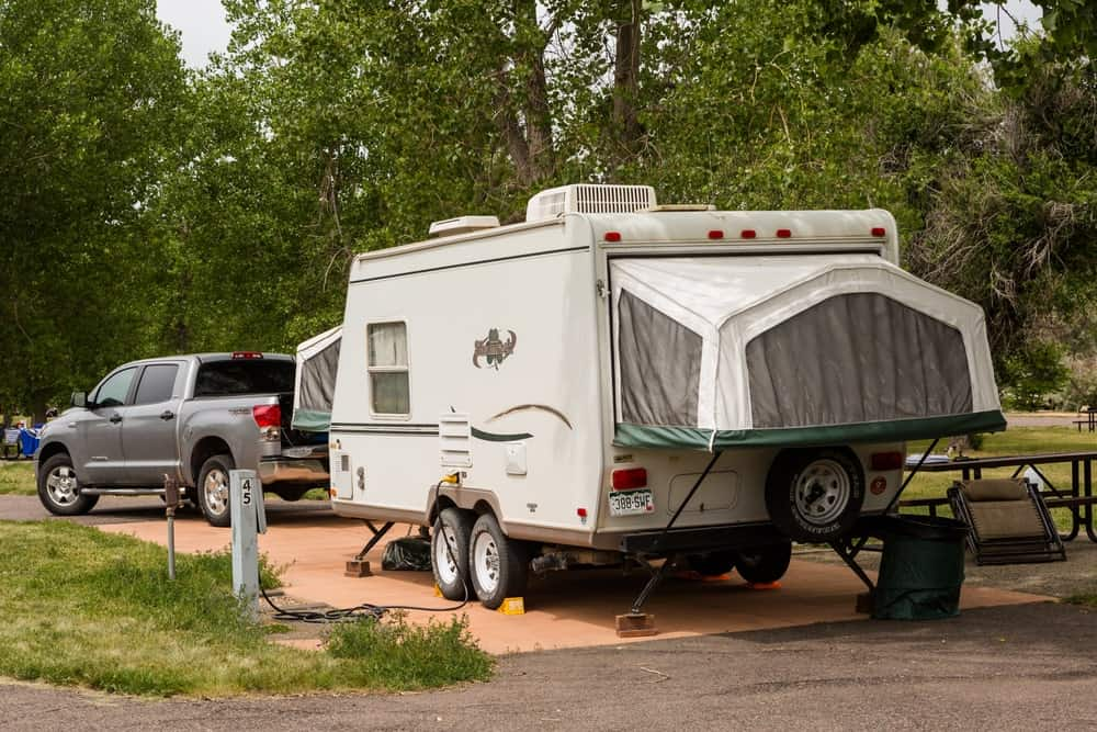 Pop-up trailer set up at campsite with pickup truck behind.