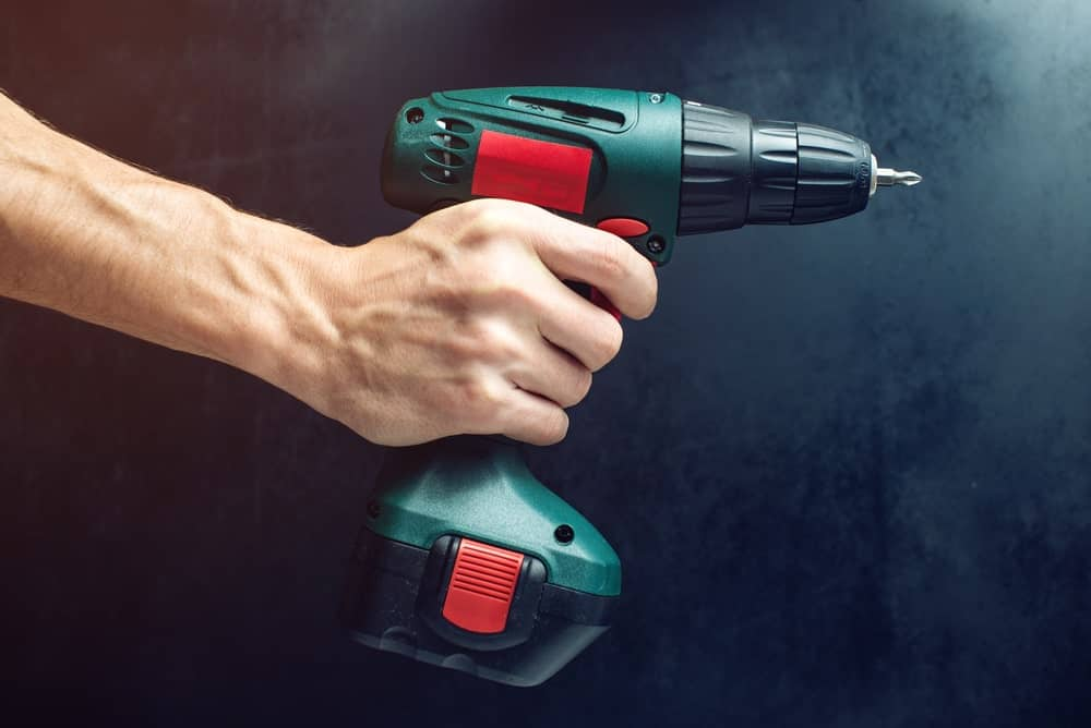 Hand holding a power drill on black background.