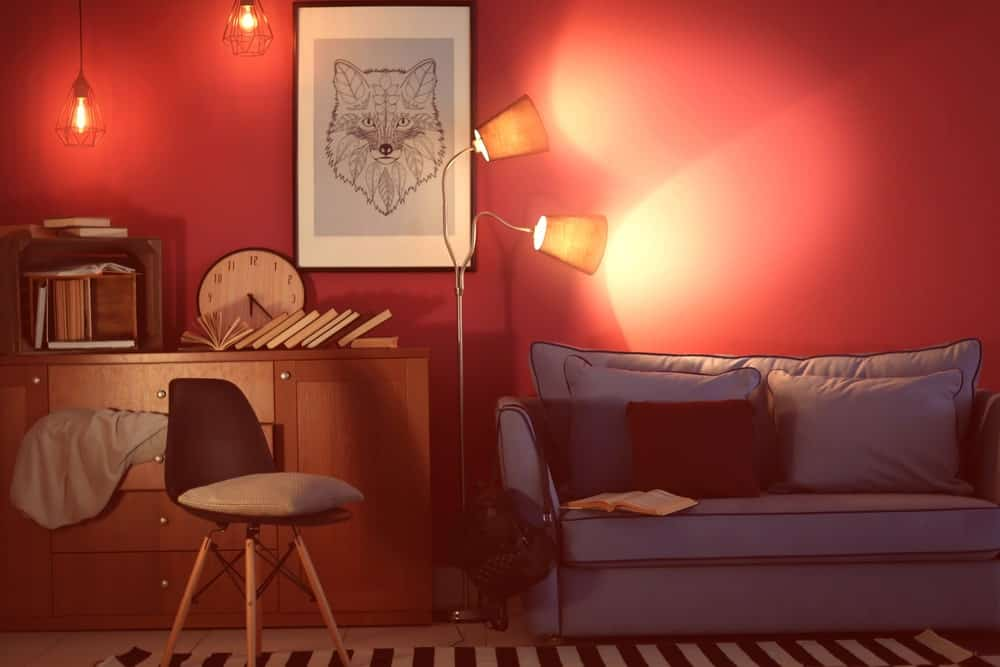 Retro-style home office and living room with pink walls, framed art, pendant vintage lights, floor lamp, and sofa.