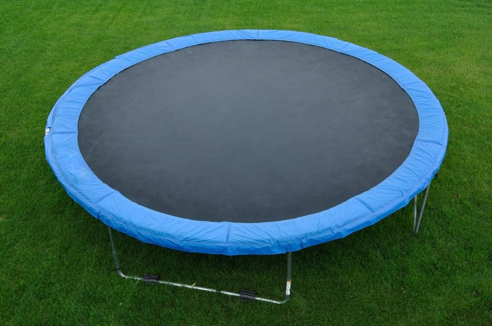 Round trampoline with a blue edge on a grassy field.