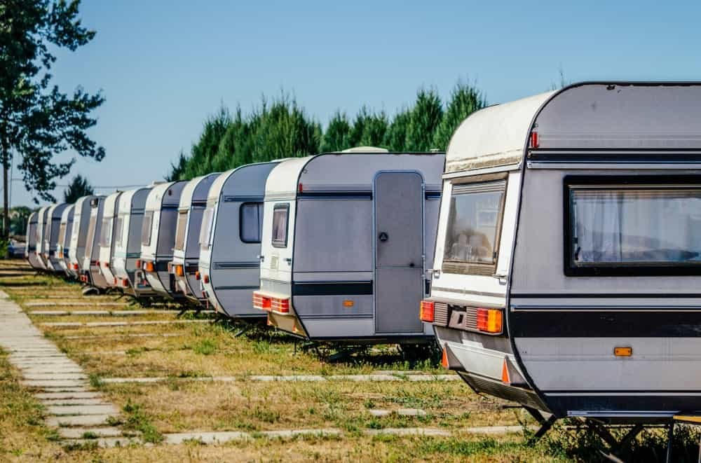 A row of RV trailers in a camping site.