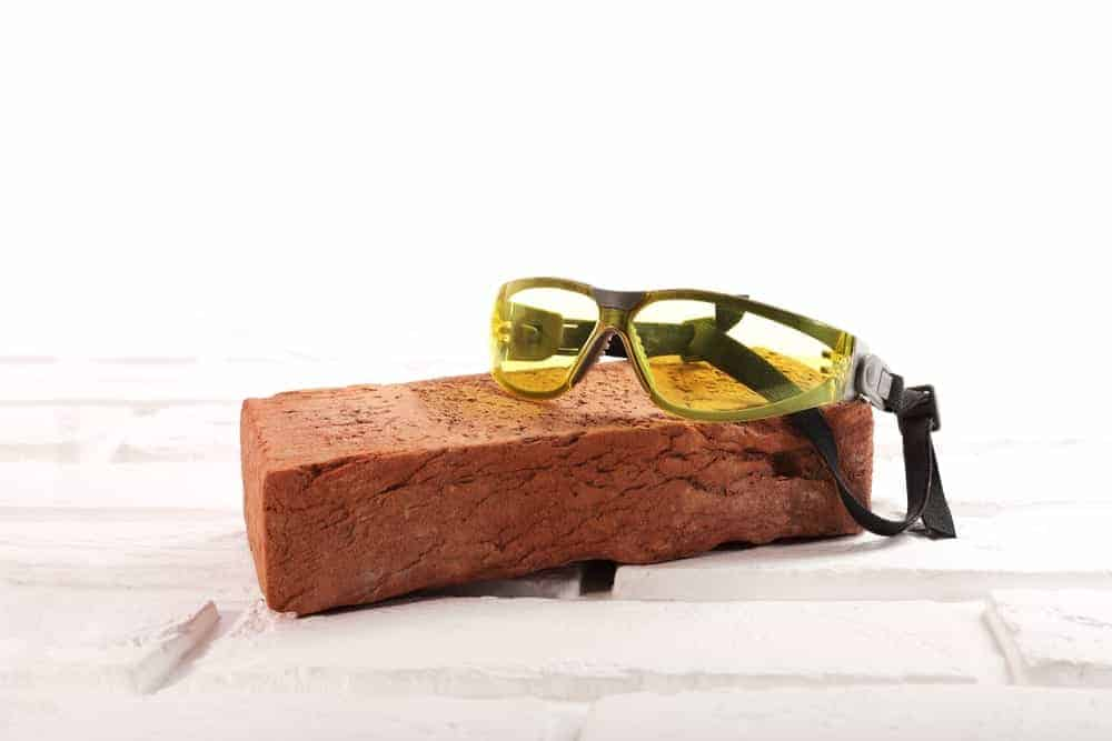 A safety goggles lies on top of a red brick on white background.