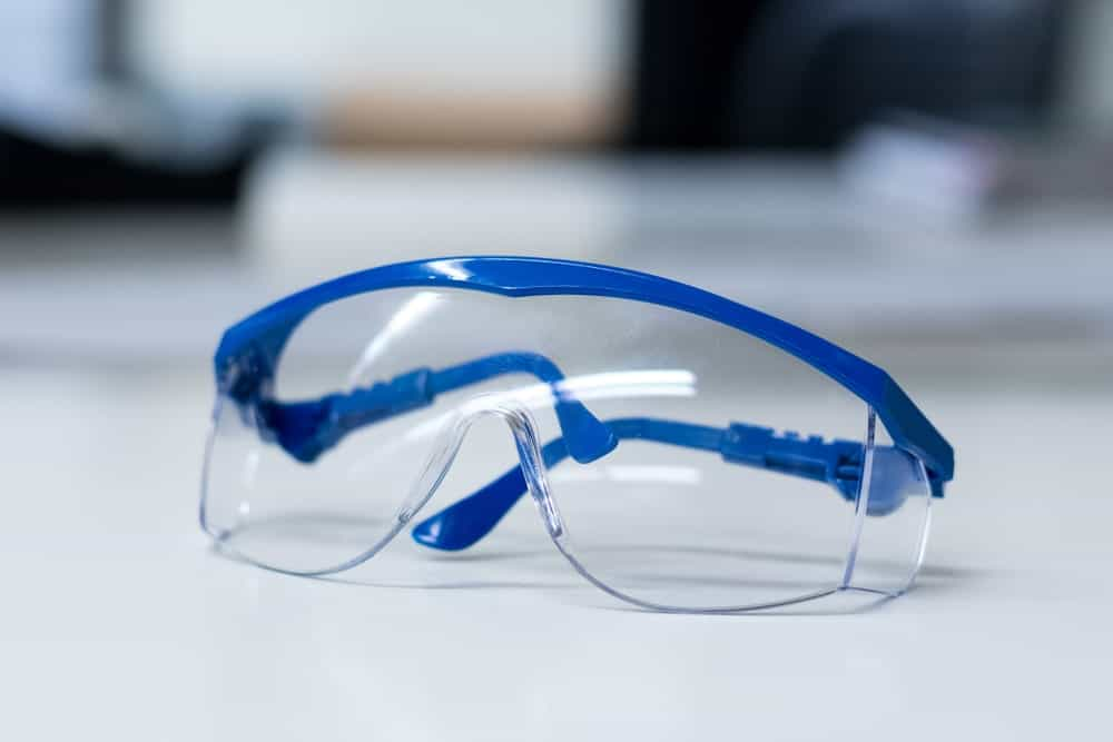 Close up of blue safety goggles on white surface.