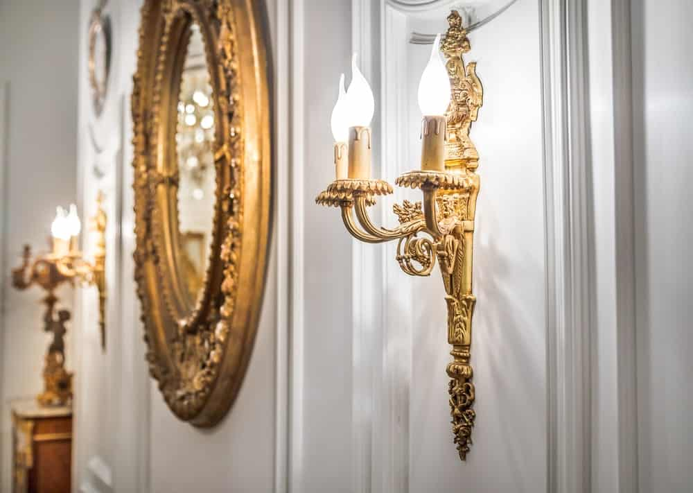 Gilded oval mirror flanked between a pair of gilded candle-style wall sconces.