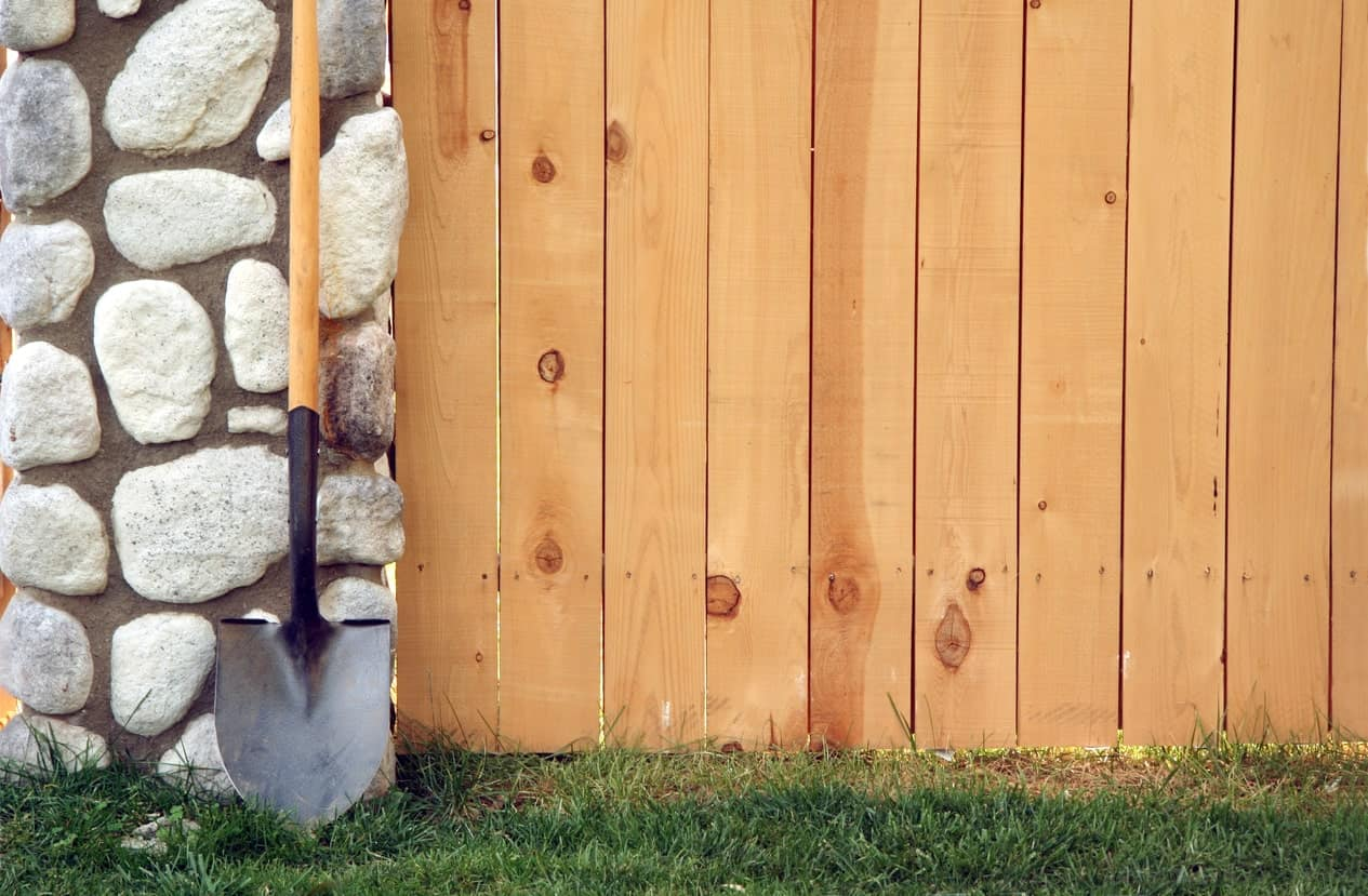 A shovel stands against a stone post beside a wooden fence.