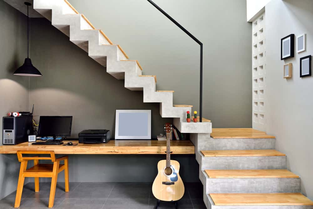 Gorgeous wood desk built into wall and concrete stairs under floating quarter-turn concrete stairs.