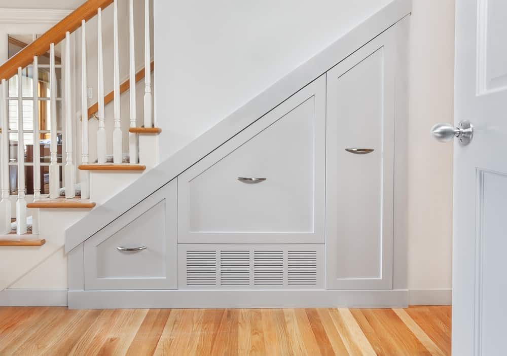 Subtle built-in under stair storage drawers in white with stainless steel hardware.