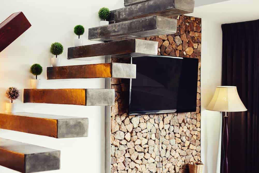 Attractive stacked firewood storage accent wall under stairs with TV mounted.