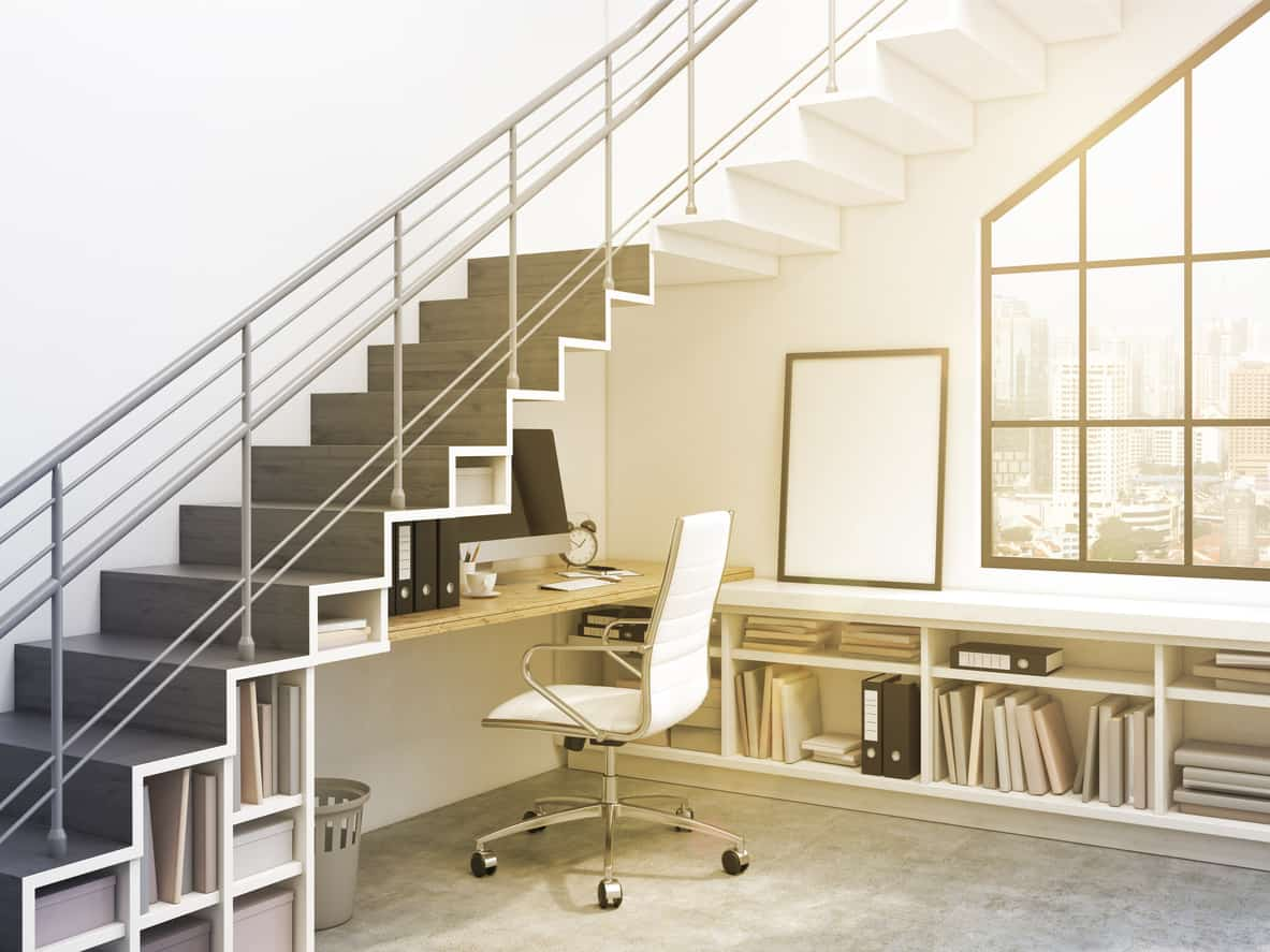 Handsome office with built-in desk and shelving under l-shaped staircase.