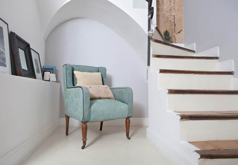 What a fabulous little reading nook under the stairs. I love that arched design and the chair. It's a super smart use below the stairs.