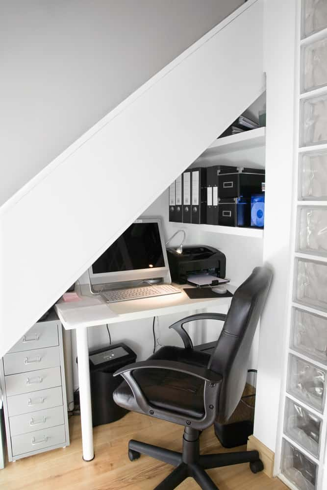 Tiny office workspace under steep staircase.