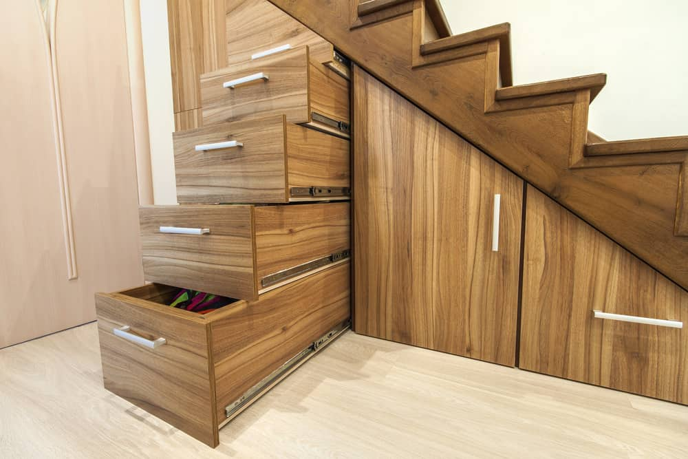 Storage under stairs that includes drawers and cupboards. Well designed for maximum storage capacity and the natural wood facing looks good.
