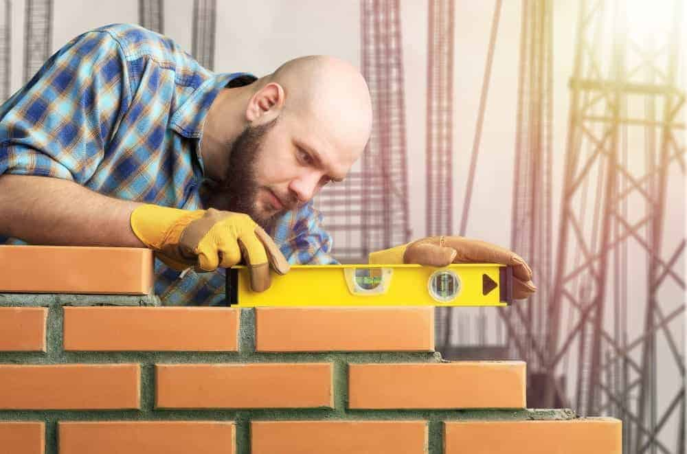 A man uses a spirit level on top of a brickwork.
