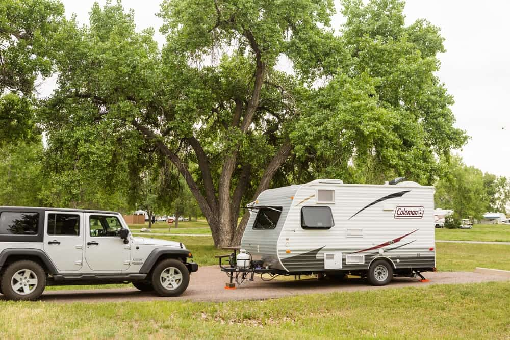 Sport utility RV trailer parked in front of a jeep at campsite.